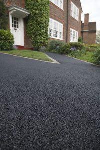 An asphalt driveway that may need repairs.
